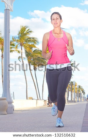 Healthy young woman jogging on a walkway against cloudy sky. Vertical Shot. - stock photo