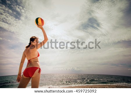 healthy young woman laughing with beachball while on the beach in summer. vacation, sport and people concept - young woman with ball playing volleyball