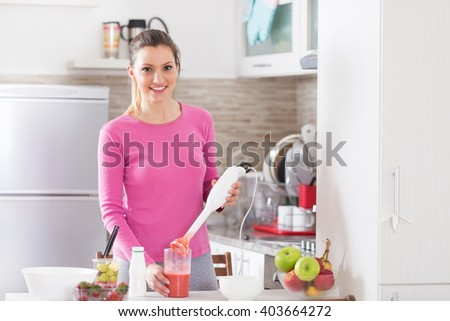 Healthy young woman making a fruit smoothie on her kitchen counter. - stock photo