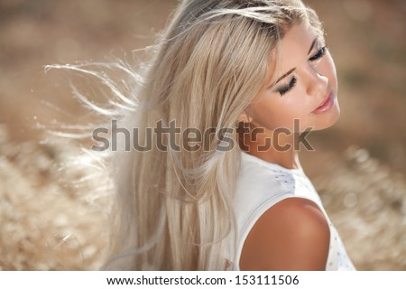 Healthy Young woman outdoors on nature. Happy smiling teenager girl at wheat field. skin and hair care. natural long blonde hair. autumn girl. Attractive pretty girl at wheat field. Sensual blonde.