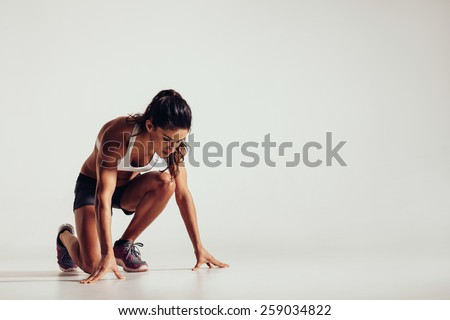Healthy young woman preparing for a run. Fit female athlete ready for a spring over grey background with copy space. - stock photo