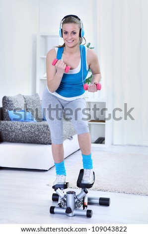 Healthy  young woman smiling and exercising at home - stock photo