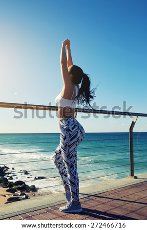 Healthy young woman stretching before her run while standing on wooden jetty with beautiful beach coastline on background,female runner warming up before a workout outdoors at sunny summer day outside - stock photo