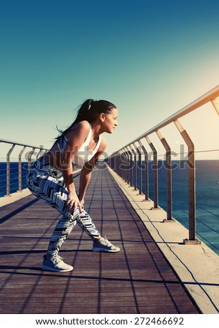 Healthy young woman stretching before her run while standing on wooden jetty with beautiful sea horizon on background, female runner warming up before a workout outdoors at sunny summer day outside - stock photo