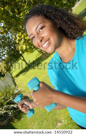 Healthy young woman with dumbbells in the park - stock photo