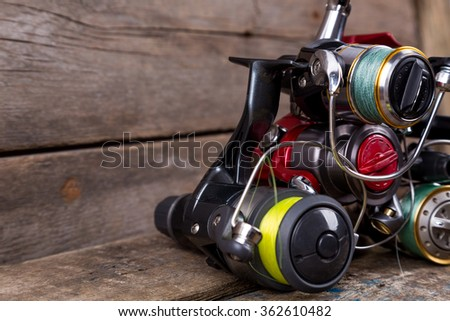 heap different fishing reels with line on wooden background. color tackles with original idea for design