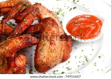 Heap fried on a grill of chicken wings with sauce and spicescocktails - stock photo