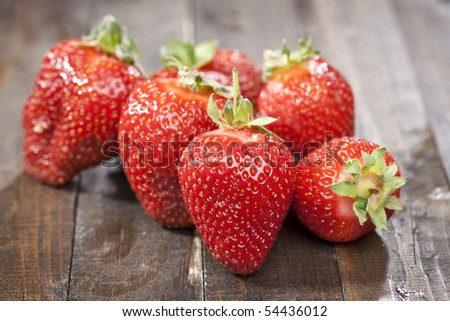 Heap of a lot of fresh red strawberries on wooden table top - stock photo