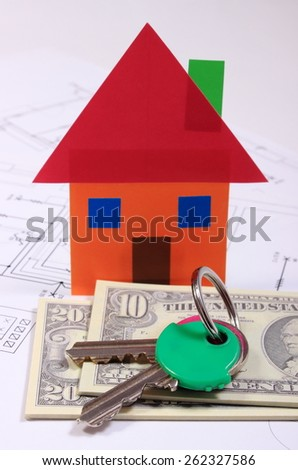 Heap of banknotes, house of colored paper and home keys on construction drawing of house, concept of building home