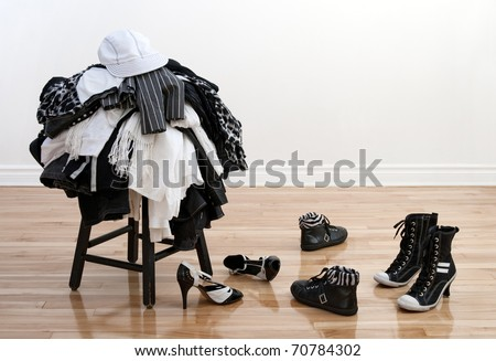 Heap of black and white clothes on a stool and disordered shoes on a wooden floor. - stock photo
