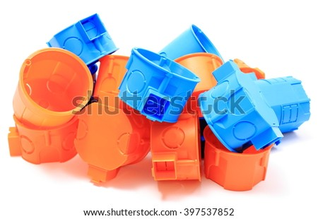 Heap of blue and orange plastic electrical boxes on white background, junction boxes, accessories for engineering jobs