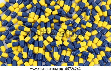 heap of blue yellow capsule background - stock photo