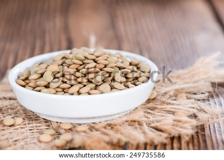 Heap of brown Lentils on wooden rustic background - stock photo