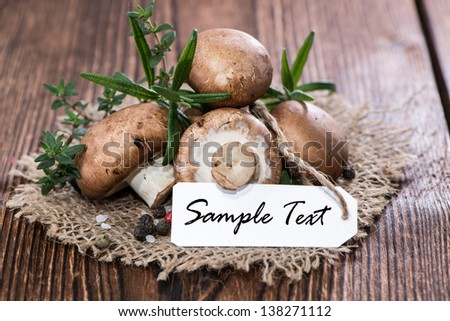 Heap of brown Mushrooms with Rosemary and Pepper on wood - stock photo