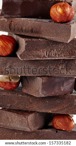 heap of chocolate pieces and whole hazelnuts on a white background