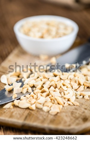 Heap of chopped Peanuts (selective focus) on vintage wooden background - stock photo