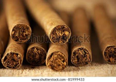 Heap of cigars on old wooden surface. - stock photo