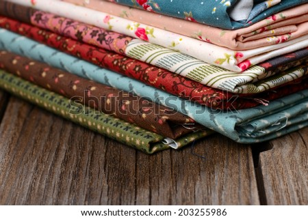 heap of cloth fabrics on wooden table - stock photo