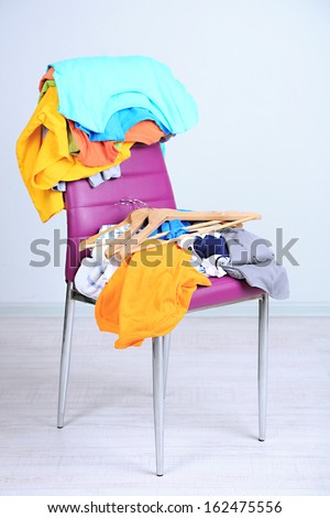Heap of  clothes on color chair,  on gray background - stock photo