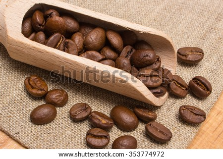 Heap of coffee beans on wooden scoop lying on jute burlap on table, coffee grains - stock photo