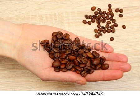 Heap of coffee grains in hand of woman, coffee beans - stock photo