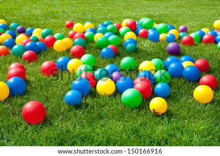 Heap of Colorful Balls on green grass. Birthday party - stock photo