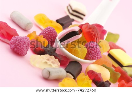 Heap of colorful candy and white ceramic spoon on pink background. - stock photo