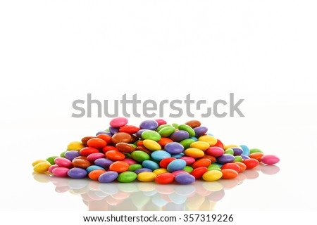 heap of colorful smarties placed in middle of picture on white background - stock photo