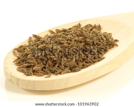 Heap of cumin served on wooden tray