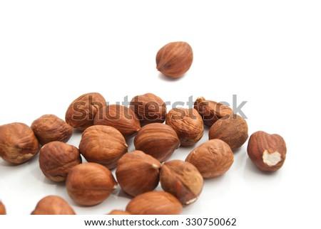 heap of delicious hazelnuts closeup on white background - stock photo