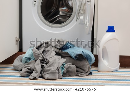 Heap of dirty clothes in front of opened washing machine - stock photo
