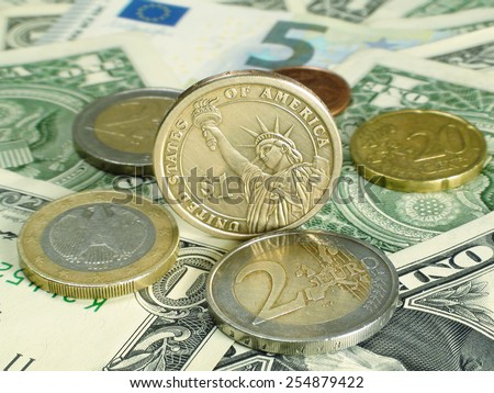 Heap of Dollar and Euro coins on money bills - stock photo