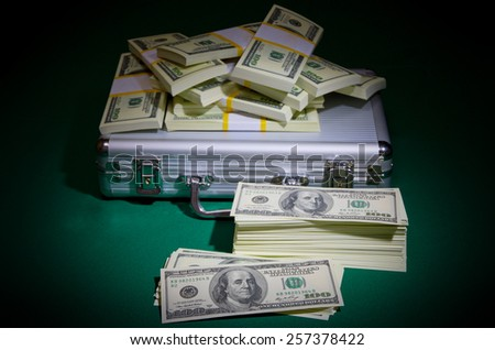 Heap of dollars on green table - stock photo