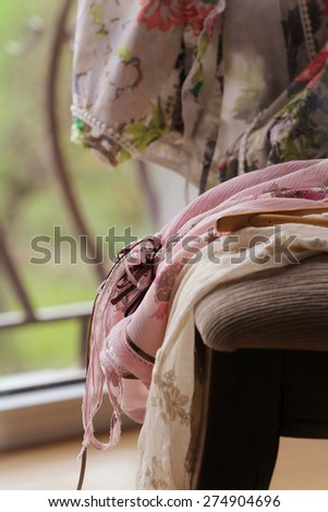 Heap of dresses on  chair - stock photo