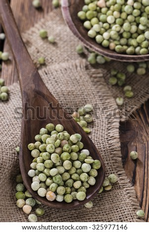 Heap of dried green Peas (close-up shot) on wooden background - stock photo