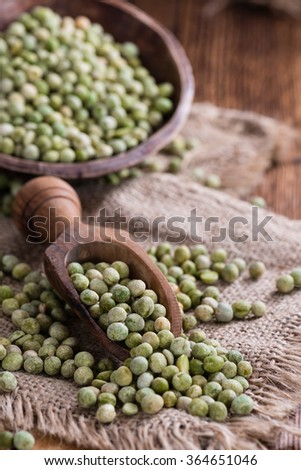 Heap of dried green Peas (close-up shot) on wooden background