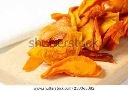 heap of dried mango slices on wooden cutting board - stock photo