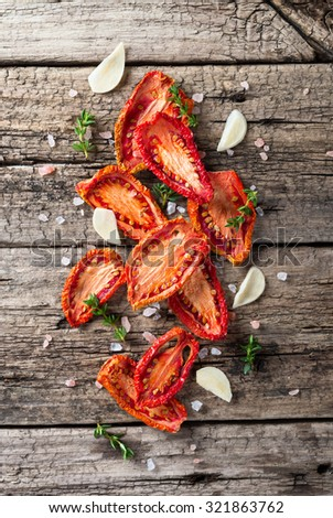 Heap of dried tomatoes on rustic wooden background - stock photo