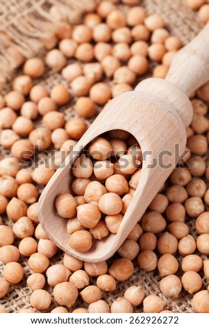 Heap of dry chick peas healthy nutrition food in wooden spoon on textile background - stock photo