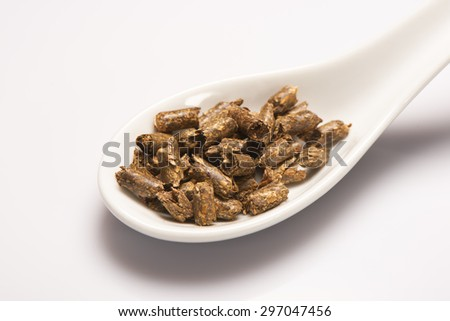 Heap of dry green medical herbal tea in white ceramic spoon on white background - stock photo