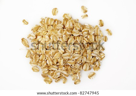 Heap of dry rolled oats on white background - stock photo