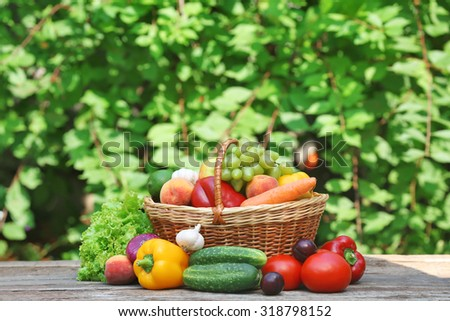 Heap of fresh fruits and vegetables in basket on table outdoors - stock photo