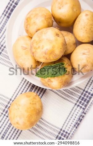 heap of fresh ripe potatoes on dish in studio - stock photo