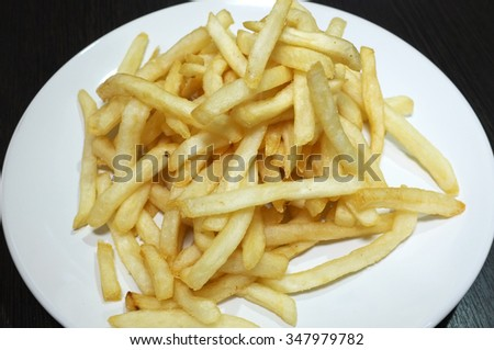 Heap of fried potato chip sticks on white dish