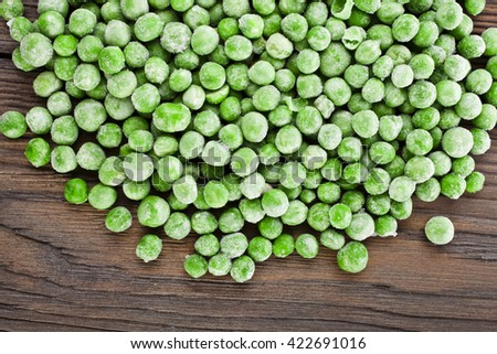 Heap of frozen pea on a old wooden table, top view. - stock photo