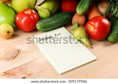 Heap of fruits and vegetables with shopping list on table close up