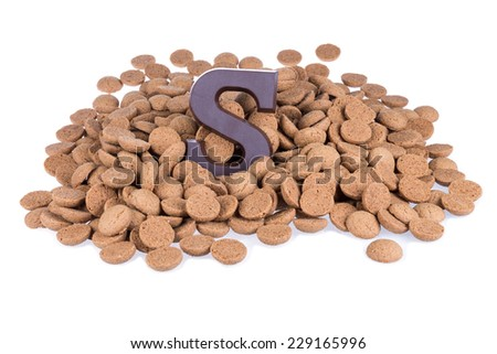 Heap of ginger nuts with chocolate letter S - stock photo