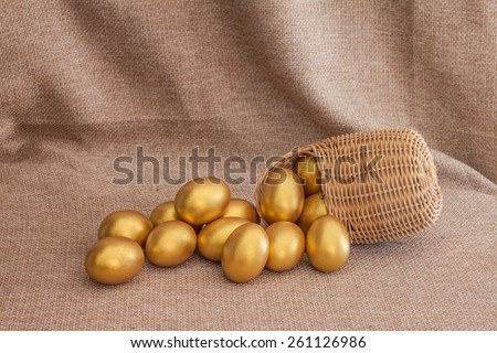 Heap of golden easter egg in wicker basket on sack background - stock photo