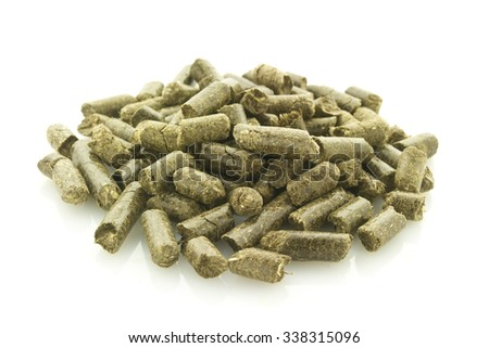 heap of grass pellets, symbol of renewable energy, isolated on white reflective background - stock photo