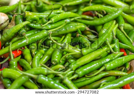 Heap of green Cayenne pepper (Capsicum annuum) is also called Guinea spice, cow-horn pepper, red hot chili pepper, aleva or bird pepper for retail sale in Thailand fresh food market - stock photo